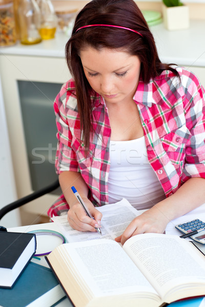 Concentrated student doing her homework at home in the kitchen Stock photo © wavebreak_media