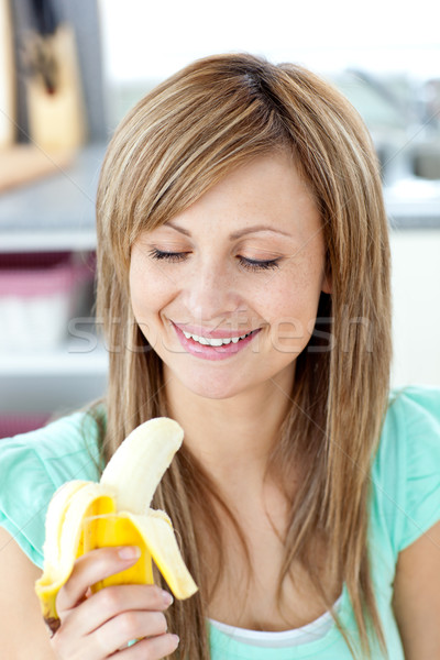 Smiling young woman holding a banana in the kitchen at home Stock photo © wavebreak_media