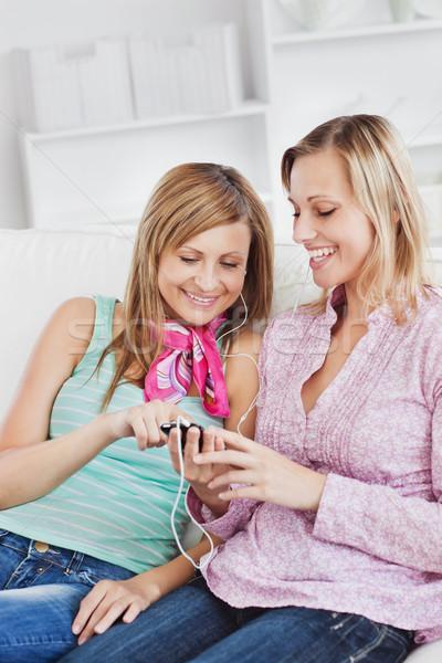 Kettő nők zenét hallgat fülhallgató mobiltelefon otthon Stock fotó © wavebreak_media