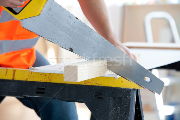 Close-up of a serious male worker sawing a wooden board at work Stock photo © wavebreak_media