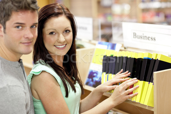Stock photo: Adorable couple looking for a business book in a library smiling at the camera
