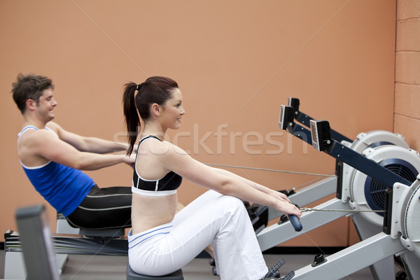 Young couple using a rower in a sport centre Stock photo © wavebreak_media