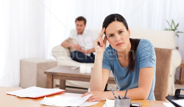 Stock photo: Worried woman doing her account while her boyfriend waiting in the living room