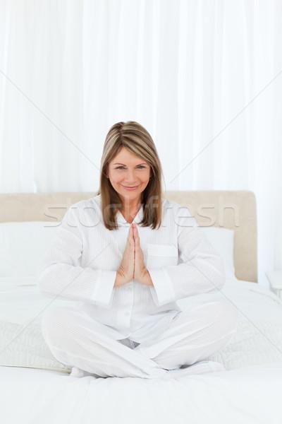 Senior practicing yoga on her bed at home Stock photo © wavebreak_media