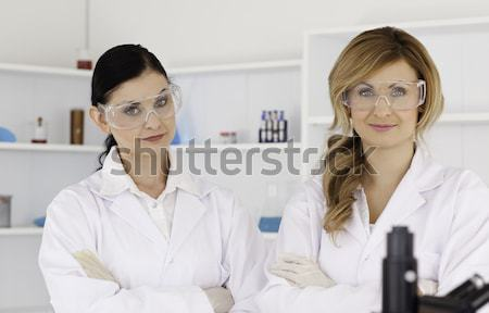 Two female scientists with safety glasses looking at the camera while standing in a lab Stock photo © wavebreak_media