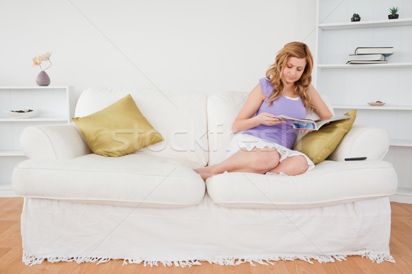 Pretty red-haired woman reading a magazine while sitting on a sofa in the living room Stock photo © wavebreak_media