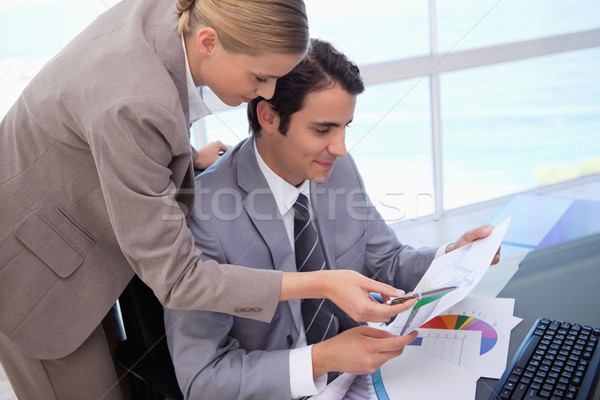 Manager pointing at something to her employee on a graph in his office Stock photo © wavebreak_media