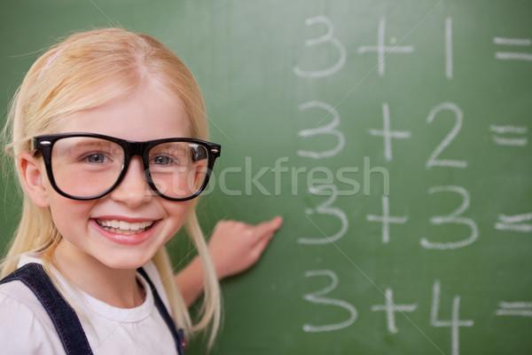 Inteligente aluna indicação algo lousa menina Foto stock © wavebreak_media