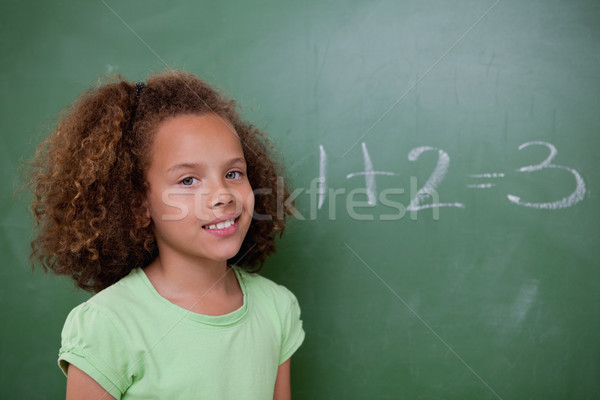 Cute schoolgirl posing in front of an addition in a classroom Stock photo © wavebreak_media