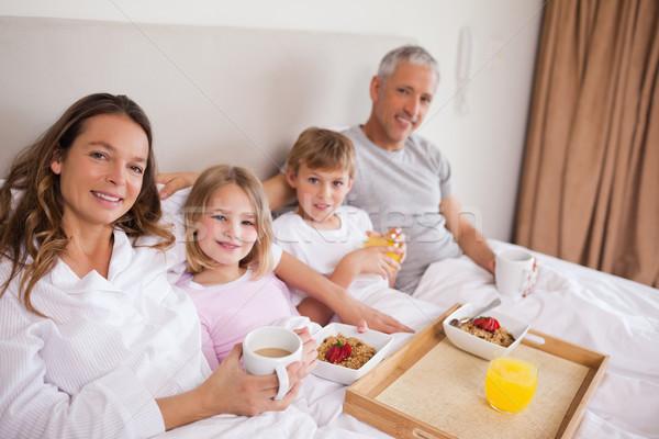 Сток-фото: счастливая · семья · завтрак · спальня · глядя · камеры · улыбка