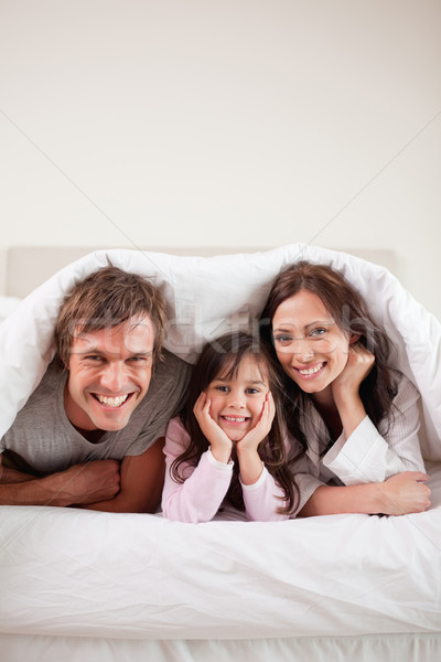 Portrait of parents lying under a duvet with their daughter in their bedroom Stock photo © wavebreak_media