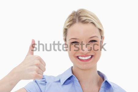 Smiling woman giving thumb up against a white background Stock photo © wavebreak_media