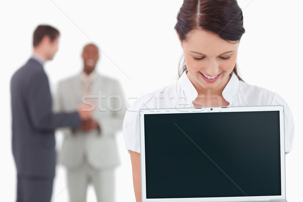 Businesswoman showing laptop with associates behind her against a white background Stock photo © wavebreak_media