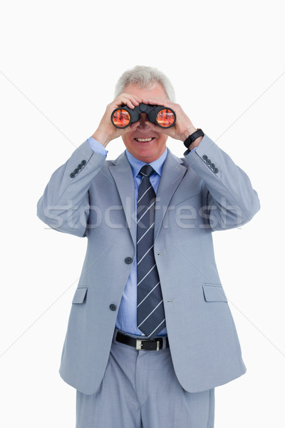 Smiling mature tradesman looking through spy glass against a white background Stock photo © wavebreak_media