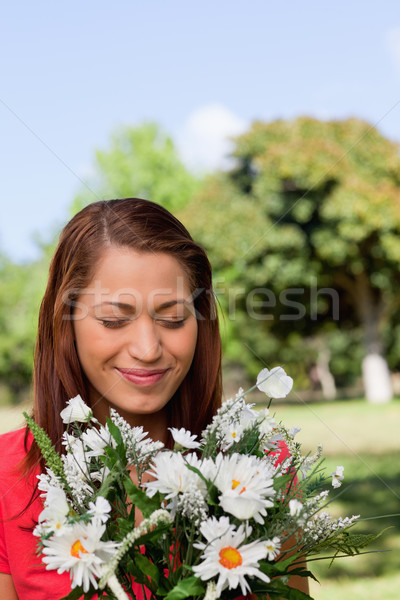 Young woman looking at a bunch of flowers while standing in a sunny parkland area Stock photo © wavebreak_media