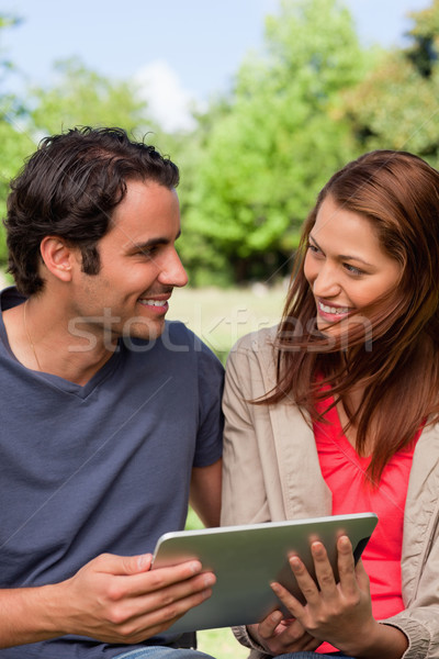 A man and a woman happily look at each other while they are holding a tablet in a bright park Stock photo © wavebreak_media