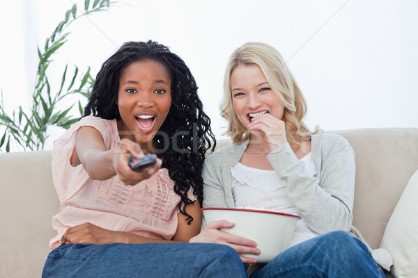 Two women are sitting down looking at the camera with popcorn and a television remote Stock photo © wavebreak_media