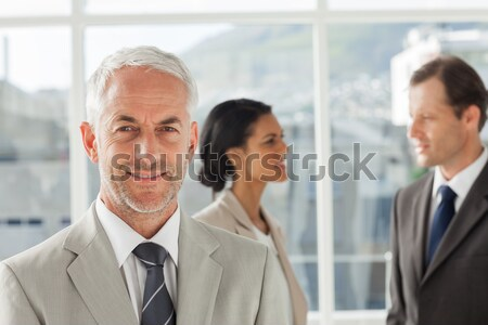 Mature smiling manager standing upright in front of his co-workers Stock photo © wavebreak_media