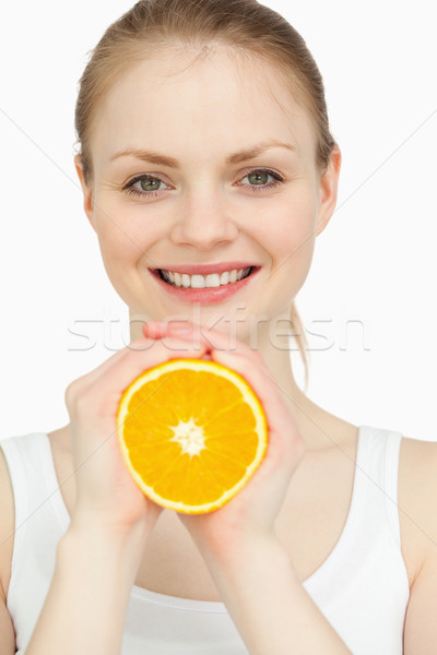 Smiling woman holding an orange in her hands against white background Stock photo © wavebreak_media