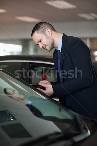 Salesman looking inside the car in a garage Stock photo © wavebreak_media