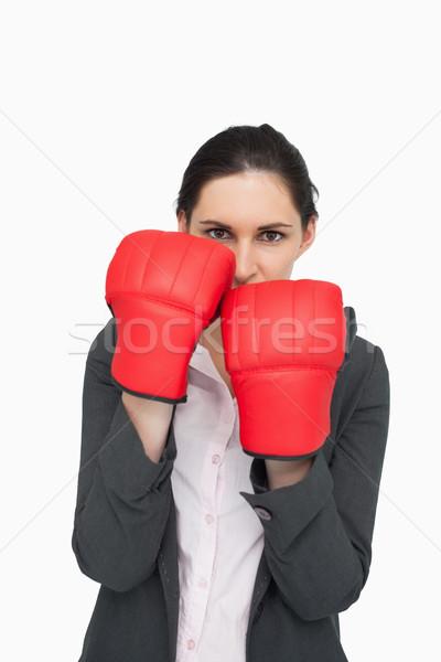 Combative brunette wearing red gloves against white background Stock photo © wavebreak_media