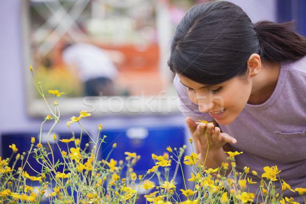 Woman smelling yellow flowers happily in garden center Stock photo © wavebreak_media