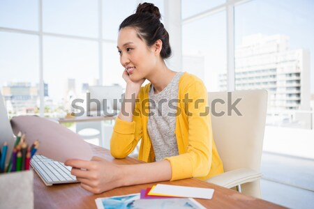 Young woman sitting on the couch in a living room and working with the laptop Stock photo © wavebreak_media