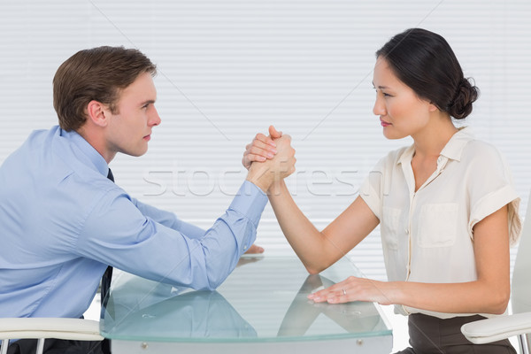 Business couple arm wrestling at desk Stock photo © wavebreak_media