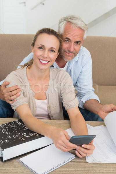 Smiling couple calculating their bills at the couch Stock photo © wavebreak_media