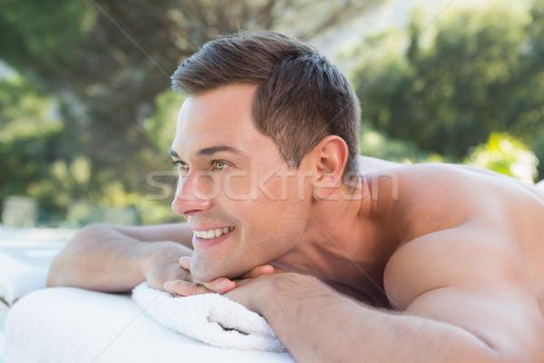 Smiling man lying on massage table poolside Stock photo © wavebreak_media