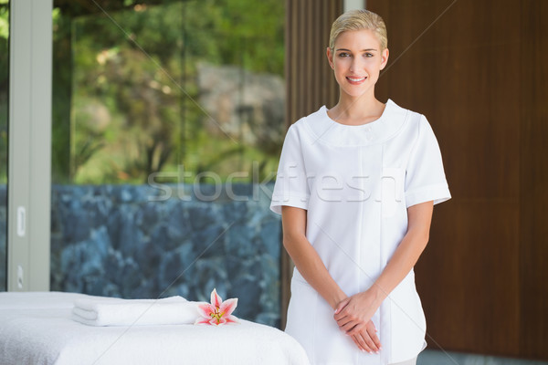 Smiling beauty therapist standing beside massage towel Stock photo © wavebreak_media