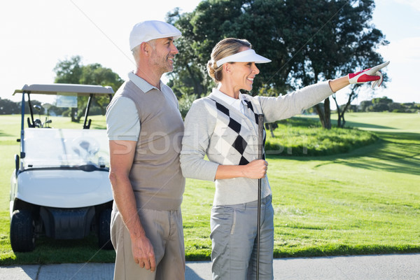 Happy golfing couple looking at course with golf buggy behind Stock photo © wavebreak_media