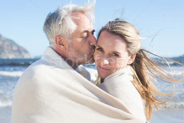 Smiling couple wrapped up in blanket on the beach Stock photo © wavebreak_media