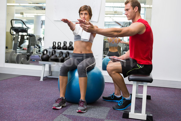 Personal trainer with client sitting straight on exercise ball Stock photo © wavebreak_media
