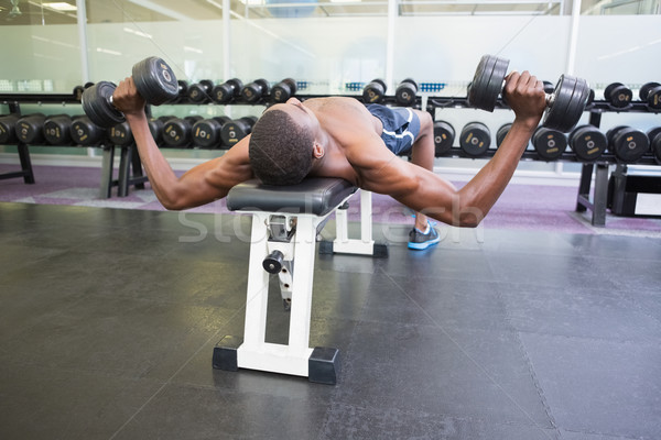 Shirtless man exercising with dumbbells in gym Stock photo © wavebreak_media