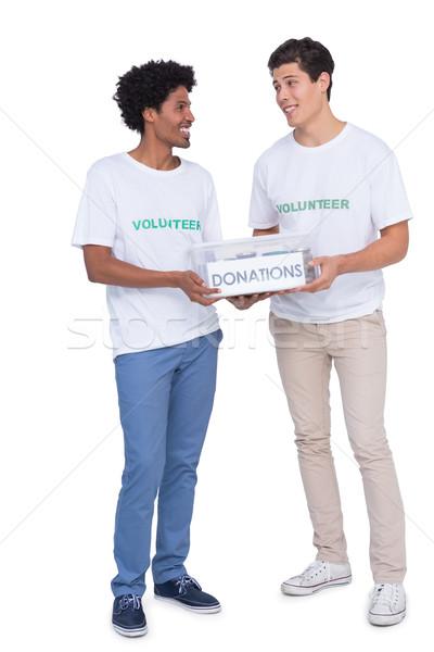 Jeunes souriant bénévoles dons blanche Photo stock © wavebreak_media