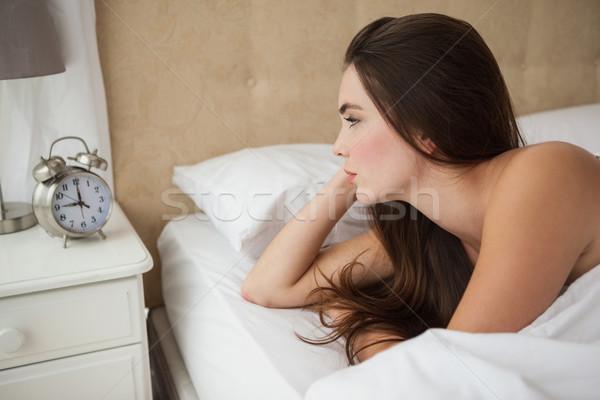 Pretty brunette looking at her alarm clock Stock photo © wavebreak_media