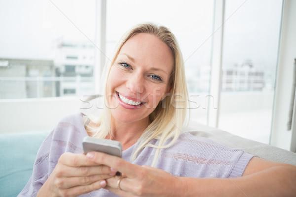 Sorrindo telefone móvel sala de estar retrato mulher Foto stock © wavebreak_media
