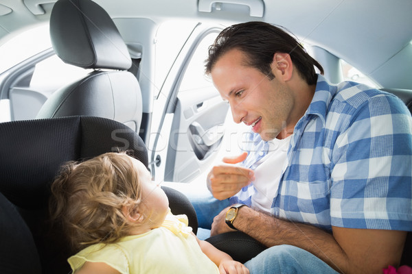 Stock photo: Father securing his baby in the car seat