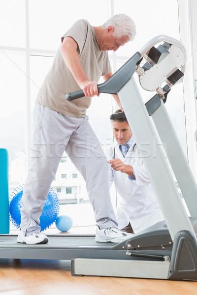 Senior man on treadmill with therapist crouching Stock photo © wavebreak_media