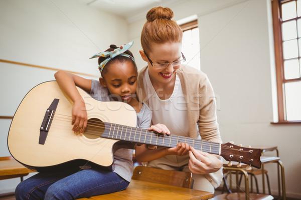 Teacher teaching girl to play guitar in classroom Stock photo © wavebreak_media