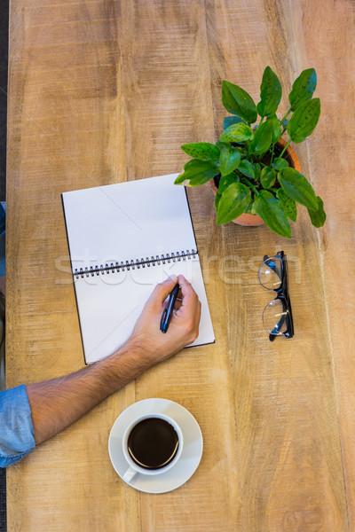 Man writing in notepad Stock photo © wavebreak_media