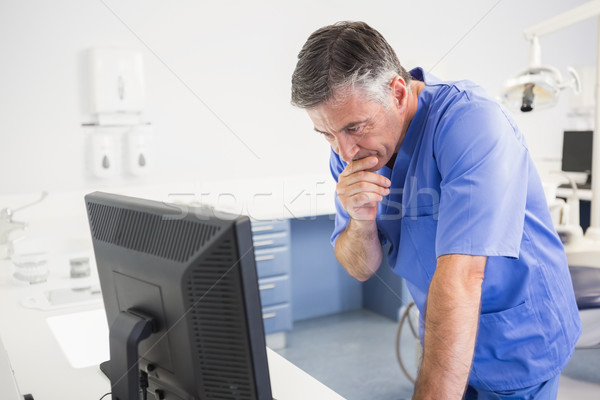 Thoughtful dentist using computer  Stock photo © wavebreak_media