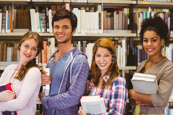Students in a line smiling at camera holding books Stock photo © wavebreak_media