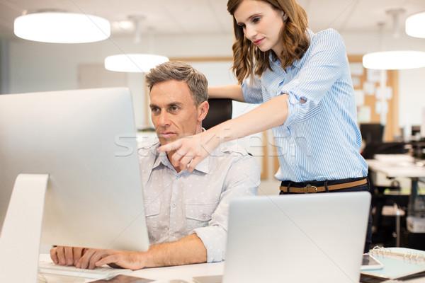 Female colleague assisting businessman working in office Stock photo © wavebreak_media