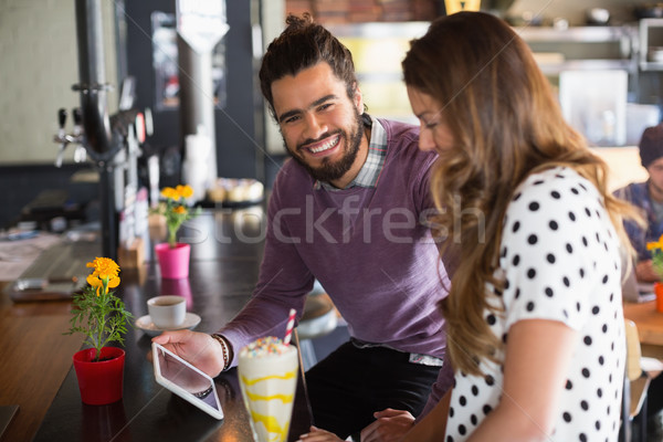Portrait of cheerful man holding digital tablet while sitting with female friend Stock photo © wavebreak_media