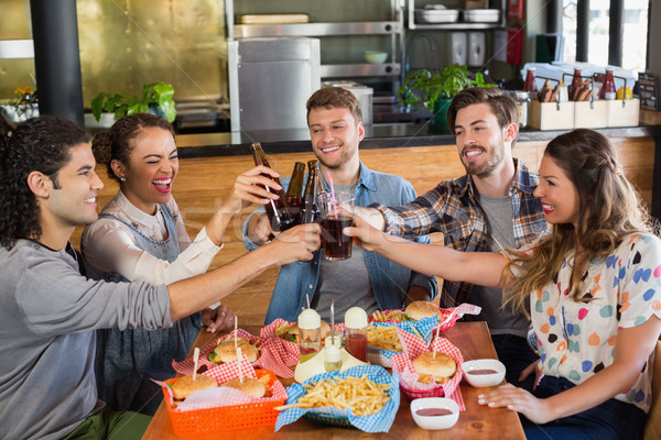 Cheerful friends toasting beer bottles in pub Stock photo © wavebreak_media