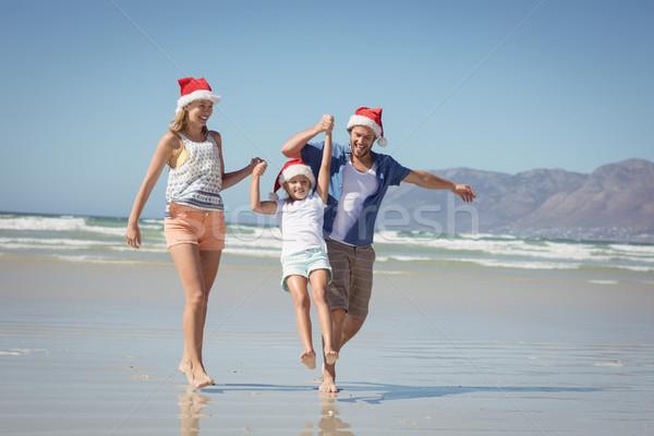 Boldog család visel mikulás kalap élvezi tengerpart Stock fotó © wavebreak_media