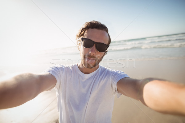 Stock photo: Portrait of young man wearing sunglasses at beach