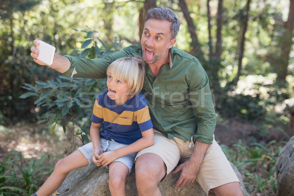 Father and son sticking out tongue while taking selfie in forest Stock photo © wavebreak_media